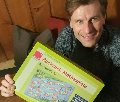 Florian Moitzi mit den Ruckzuck-Mathespielen in der Hand.